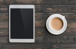 咖啡杯和片剂个人计算机相似与在黑暗的木台式视图的ipad 图库摄影