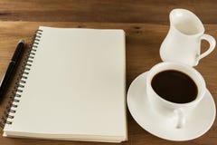 咖啡杯和牛奶与日志笔记关于桌木葡萄酒backgr 库存图片