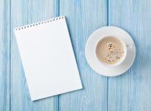 咖啡杯和空白的笔记薄 免版税库存照片