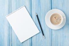 咖啡杯和空白的笔记薄 库存图片