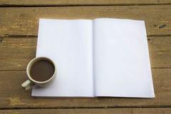 咖啡杯和笔记本在木桌上 免版税图库摄影