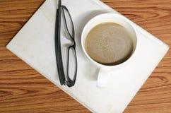 咖啡杯和笔记本有玻璃的 免版税库存照片