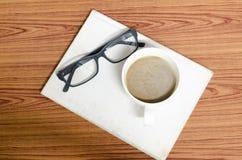 咖啡杯和笔记本有玻璃的 免版税库存图片