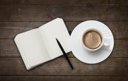 咖啡杯和笔记本 免版税库存照片