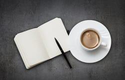 咖啡杯和笔记本 免版税图库摄影