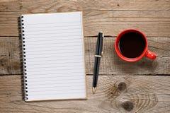 咖啡杯和笔记薄与笔 库存图片