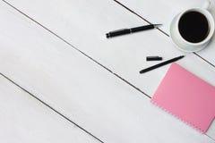 咖啡杯和笔,在白色木书桌上的笔记本和有拷贝s 库存图片