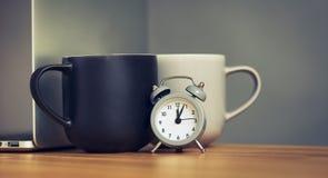 咖啡杯和膝上型计算机在办公室桌里 库存图片