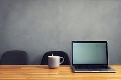 咖啡杯和膝上型计算机在办公室桌里 库存照片