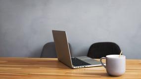 咖啡杯和膝上型计算机在办公室桌里 免版税库存照片