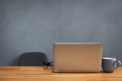 咖啡杯和膝上型计算机在办公室桌里 免版税库存图片