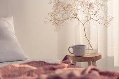 咖啡杯和花特写镜头在玻璃花瓶在明亮的卧室内部床头柜上  免版税库存照片