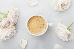 咖啡杯和葡萄酒玫瑰色花为在灰色石桌上的早晨好在舱内甲板从上面放置样式 美丽的早餐 免版税库存图片