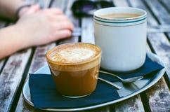 咖啡杯和蛋糕在一张木葡萄酒桌上 行家概念 妇女饮料咖啡 杯americano和macchiato 库存图片