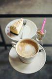咖啡杯和蛋糕在玻璃桌上 库存照片