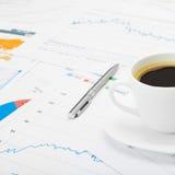 咖啡杯和计算器在世界地图和某一财政图-接近的射击 库存图片
