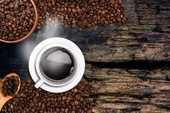 咖啡杯和豆在老木桌上 您的文本的拷贝空间 免版税库存照片