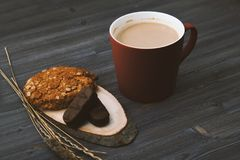 咖啡杯和饼干在一张黑暗的木桌上 免版税库存照片