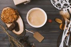 咖啡杯和饼干在一张黑暗的木桌上 库存图片