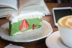 咖啡杯和鲜美蛋糕放松时间书和mobille电话在ta 免版税库存照片
