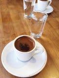 咖啡杯和水在木桌上 免版税库存图片