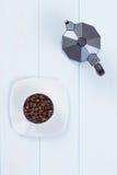 咖啡杯和moka罐用咖啡豆在桌上 免版税图库摄影