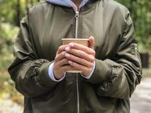 咖啡杯在妇女手上在公园 免版税库存照片