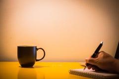咖啡杯在桌上的笔记本和膝上型计算机和手文字与la 库存照片