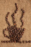 咖啡杯在粗麻布做ââof咖啡豆 库存照片