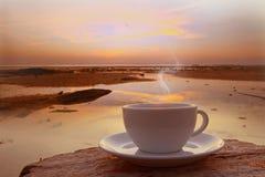 咖啡杯在面对海景的大阳台的早晨 免版税库存照片
