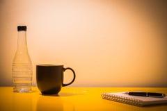 咖啡杯塑料瓶和笔记本在桌上与灯在nig 库存图片