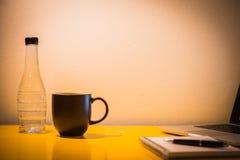 咖啡杯塑料瓶和膝上型计算机在桌上与灯在晚上 库存照片