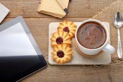 咖啡杯子用在桌和片剂上的嘎吱咬嚼的曲奇饼 免版税库存图片