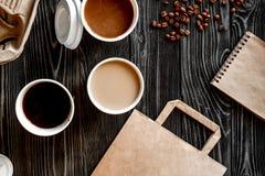 咖啡杯拿走在木背景顶视图 免版税图库摄影