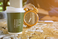 咖啡杯时钟和报纸在桌上运转 免版税库存图片