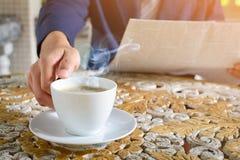 咖啡杯时钟和报纸在桌上运转 免版税库存照片