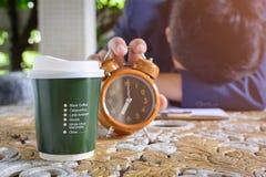 咖啡杯时钟和报纸在桌上运转 库存图片