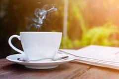 咖啡杯时钟和新闻纸在老木桌自然backg 免版税库存图片