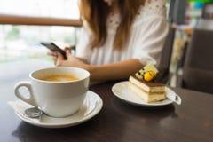 咖啡杯是在使用她巧妙的电话的妇女前面 库存图片