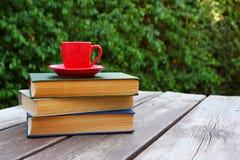 咖啡杯杯子和书在户外木桌 选择聚焦 免版税库存图片