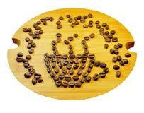 咖啡杯标志由咖啡种子(豆)制成在木盘 免版税库存图片
