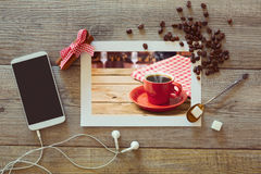 咖啡杯照片在木桌上的与聪明的电话和咖啡豆 在视图之上 免版税图库摄影