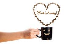 咖啡杯用咖啡豆塑造了与早晨好标志的心脏 免版税库存照片