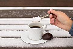 咖啡杯用在一条多雪的长凳的一个蛋白软糖 库存图片