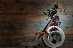 咖啡杯用在木桌上的肉桂条 免版税库存照片