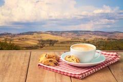 咖啡杯用在木桌上的biskotti曲奇饼在托斯卡纳风景背景 库存照片