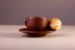 咖啡杯用在桌上的新月形面包 免版税库存图片