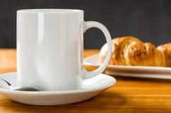 咖啡杯用在黑暗的背景的新月形面包 库存照片