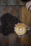 咖啡杯用心形的咖啡豆在背景中 免版税库存图片