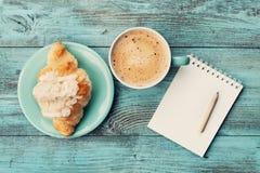 咖啡杯用新月形面包和空的笔记本和铅笔经营计划和设计想法的在绿松石土气桌上从上面 图库摄影